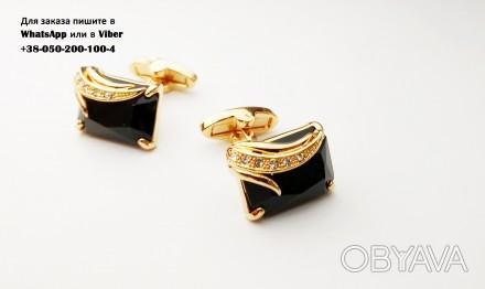 Золотистые запонки с черным камнем.